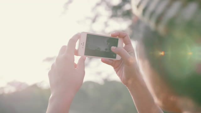 stockvideo's en b-roll-footage met toeristen fotograferen van de prachtige natuur bij zonsondergang. - fotografie