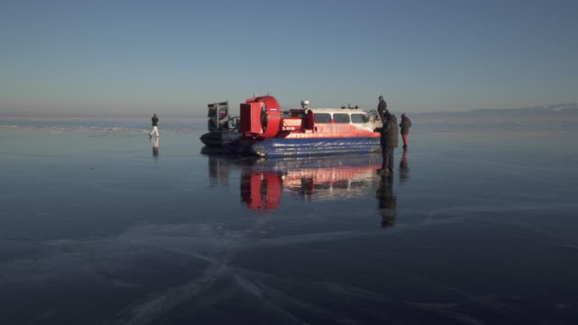 tourists photographing while standing by hovercraft on frozen lake baikal against sky - hovercraft stock videos & royalty-free footage