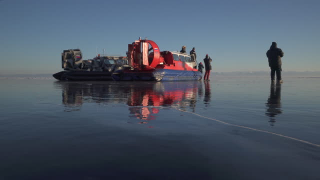 tourists photographing while standing by hovercraft over frozen lake baikal - hovercraft stock videos & royalty-free footage