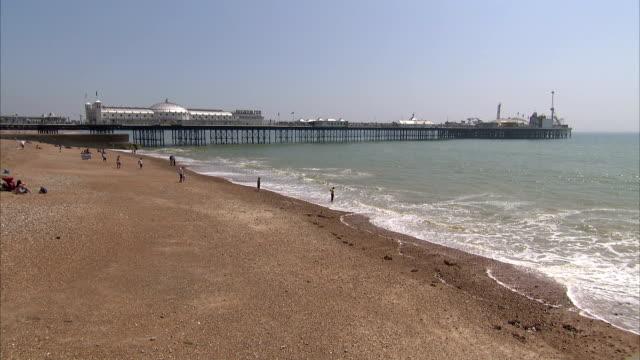 tourists play on the beach near the brighton pier. available in hd. - ブライトン パレスピア点の映像素材/bロール