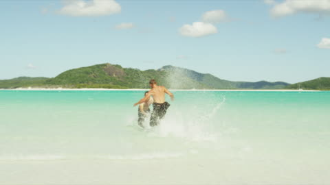 tourists play on whitehaven beach - male friendship stock videos & royalty-free footage