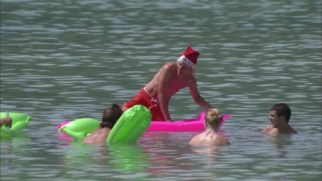 vídeos de stock e filmes b-roll de tourists playing in the sea. - chapéu do pai natal