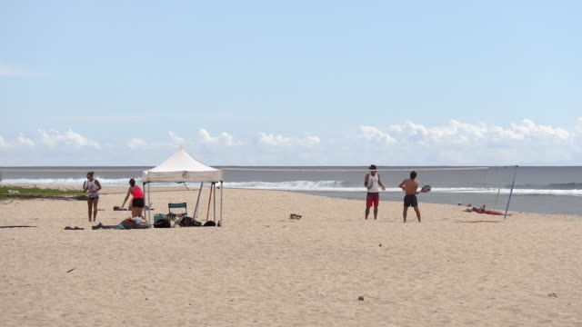 stockvideo's en b-roll-footage met ws tourists playing sports on beach, reunion island - french overseas territory