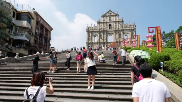 tourists pose for photographs at the ruins of st. paul's cathedral in macau, china, on wednesday, sept. 27, 2017. - 聖ポール天主堂跡点の映像素材/bロール