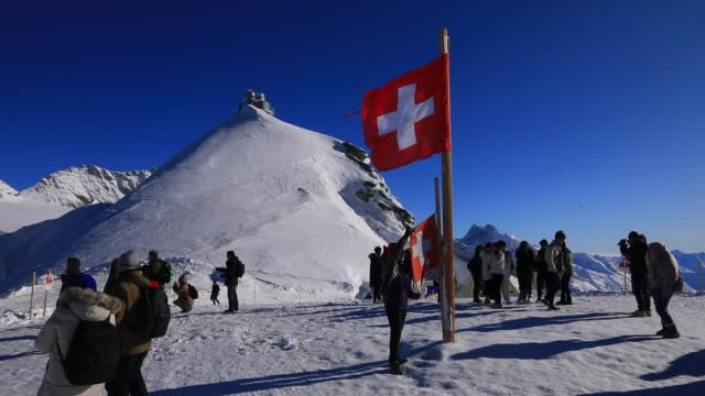 tourists poses next to the swiss flag at jungfraujoch highest railway station in europe in the bernese alps mountain range on december 3 2019 in... - sezione superiore video stock e b–roll