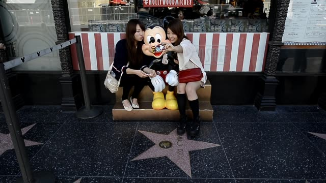 stockvideo's en b-roll-footage met tourists posing with mickey mouse statue at hollywood boulevard california on march 11 2013 in hollywood california scenes from hollywood boulevard... - hollywood walk of fame