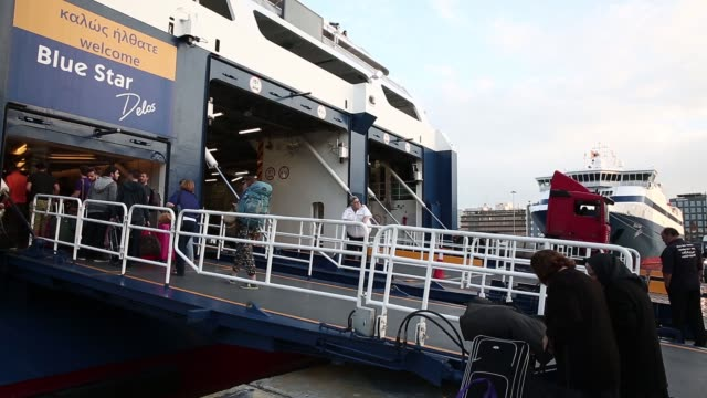 Tourists prepare to board a passenger ferry operated by Blue Star Ferries Maritime SA before it departs to the Aegean islands from the port of...