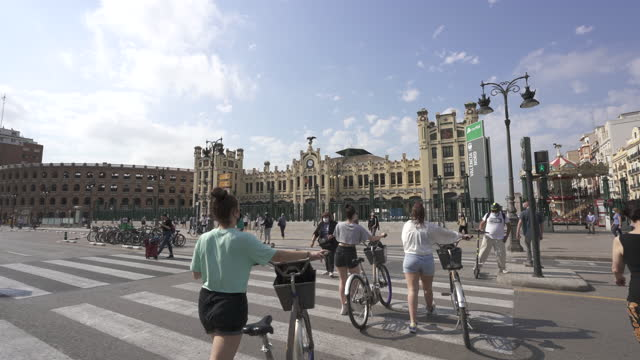 tourists pushing their urban bicycles towards valencia railway station - local landmark stock videos & royalty-free footage