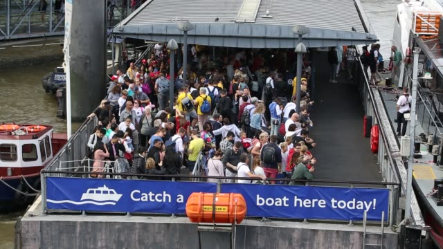 tourists queue to get on a tour boat on the river thames london uk - pier stock videos & royalty-free footage