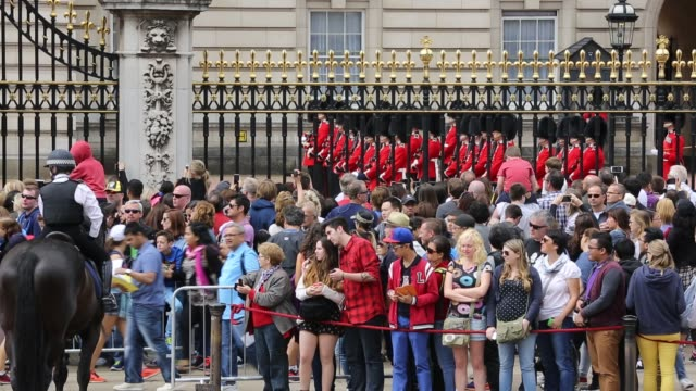 tourists queue to watch the changeing of the guard at buckingham palace, london, uk. - military parade stock videos & royalty-free footage