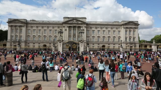 tourists queue to watch the changeing of the guard at buckingham palace, london, uk, with a plane flying over. - tourism stock videos & royalty-free footage