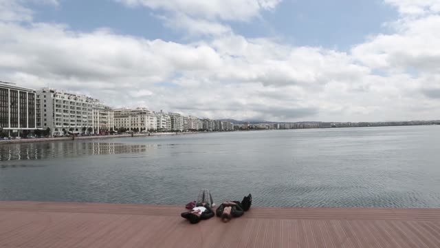tourists relax beside the sea on the waterfront in thessaloniki greece on monday april 6 gvs of tourists in thessaloniki the greek national flag... - greek flag stock videos & royalty-free footage