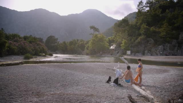 tourists relax by the coastline beach - olympos, turkey - asciugamano video stock e b–roll