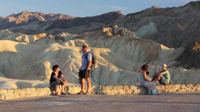 tourists relaxing at sunset amongst badland scenery at zabriskie point in death valley which is the lowest hottest driest place in the usa with an... - zabriskie point stock videos & royalty-free footage