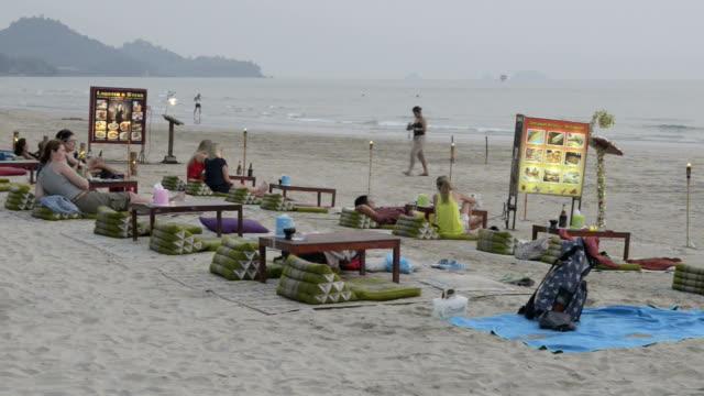 vídeos de stock e filmes b-roll de tourists relaxing in open air restaurant at sandy beach in the evening - sinal comercial