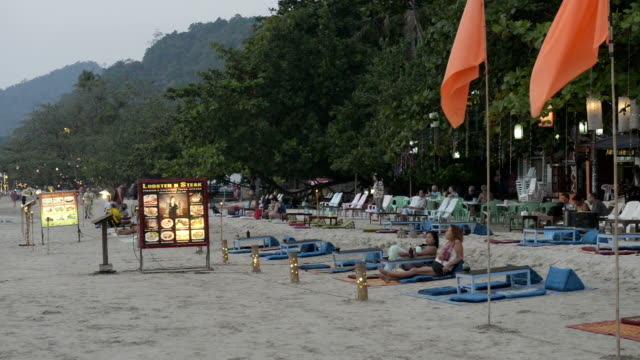 tourists relaxing in open air restaurant at sandy beach in the evening - trat province stock videos and b-roll footage