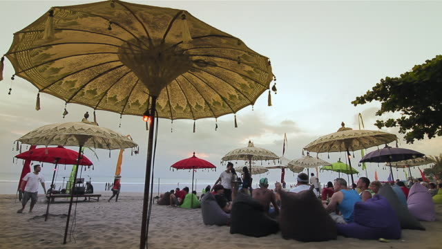 MS Tourists relaxing on beanbags below ornate umbrellas on beach  / Seminyak, Bali, Indonesia