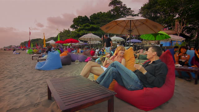 ms tourists relaxing on beanbags below ornate umbrellas on beach  / seminyak, bali, indonesia - bean bag stock videos & royalty-free footage