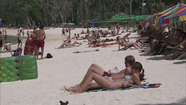 tourists relaxing on the beach: long shot. - inselgruppe phi phi stock-videos und b-roll-filmmaterial