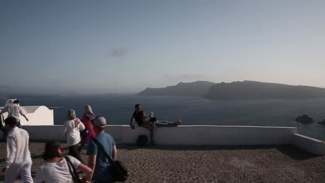 tourists rest on a wall by the aegean sea in the town of fira on the island of santorini greece on wednesday may 20 2015 shots tourists explore the... - insel santorin stock-videos und b-roll-filmmaterial