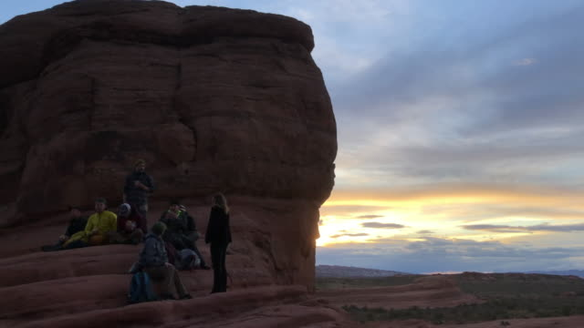 tourists resting at the arches national park in america at sunset - natural arch stock videos & royalty-free footage