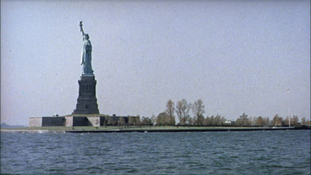 Tourists ride a boat through New York Harbor and look at the attractions.