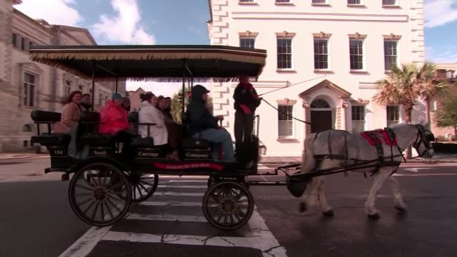 vídeos y material grabado en eventos de stock de tourists ride horse drawn carriage down street in charleston, south carolina. zoom out, pan right to follow carriage. - huma abedin