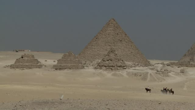 Tourists ride horses among the pyramids in the Giza Necropolis. Available in HD.