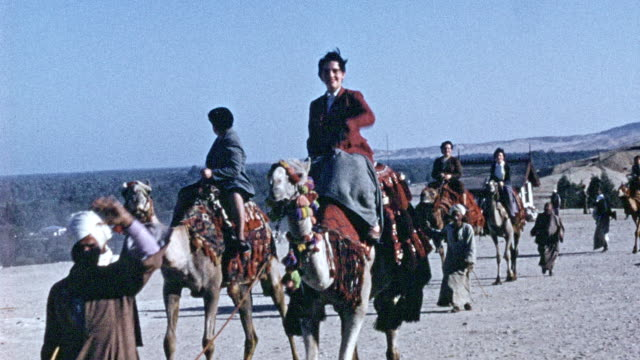 tourists ride on some camels, we can see the pyramids in the horizon - 1946 stock videos & royalty-free footage