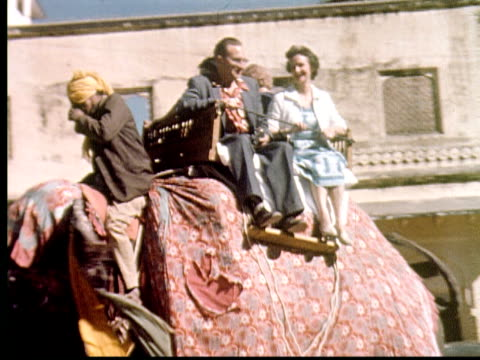 stockvideo's en b-roll-footage met 1960 montage tourists riding elephant. pov down street from top of elephant / india - sociale geschiedenis