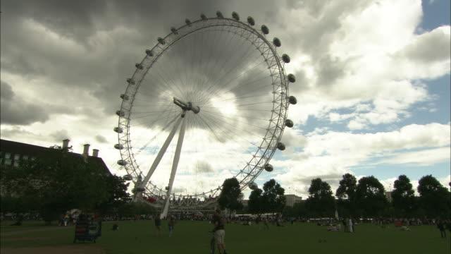 Tourists roam through a park near the London Eye.