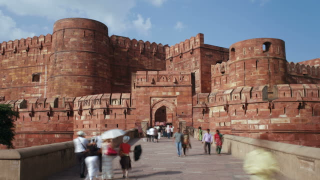 tourists share a walkway as they visit the red fort in old delhi. - モデスト・ファッション点の映像素材/bロール