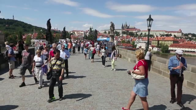tourists sit at café tables next to the vltava river in prague czech republic on monday aug 12 tourists look out at the view from the charles bridge... - charles bridge stock videos and b-roll footage
