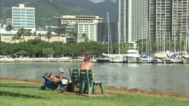tourists sit on a bench that faces a marina in honolulu. - sun visor stock videos & royalty-free footage