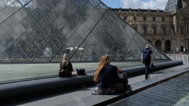 tourists sitting next to louvre pyramid paris îledefrance france on tuesday july 30 2019 - île de france stock-videos und b-roll-filmmaterial