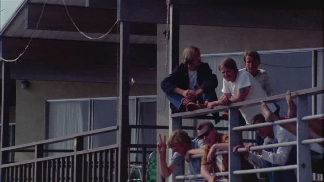 ms tourists sitting on railing / newport beach, california, usa - 1966 stock-videos und b-roll-filmmaterial