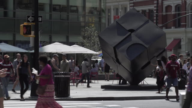 Tourists spin the Astor Place Cube on summer day in New York City.