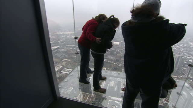 tourists stand nervously on the glass floor of a viewing platform high on chicago's sears tower. - willis tower stock videos & royalty-free footage