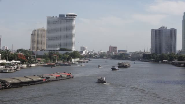 vídeos de stock, filmes e b-roll de tourists stand on the deck of a tourist boat on the chao phraya river as it navigates past the peninsula hotel center in bangkok thailand wide shots... - rio chao phraya