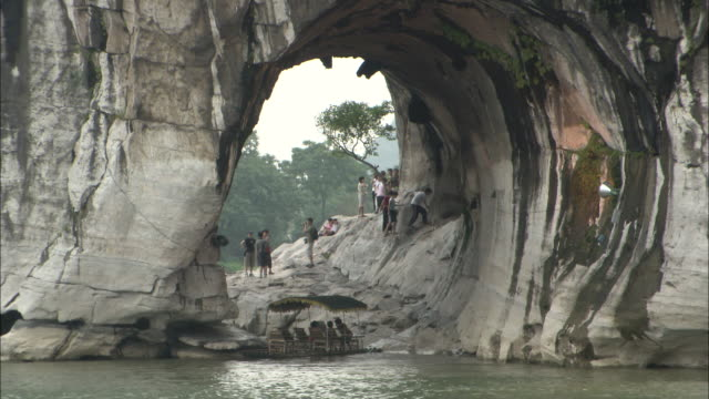Tourists stand under arch of Elephant Trunk Hill on Li River
