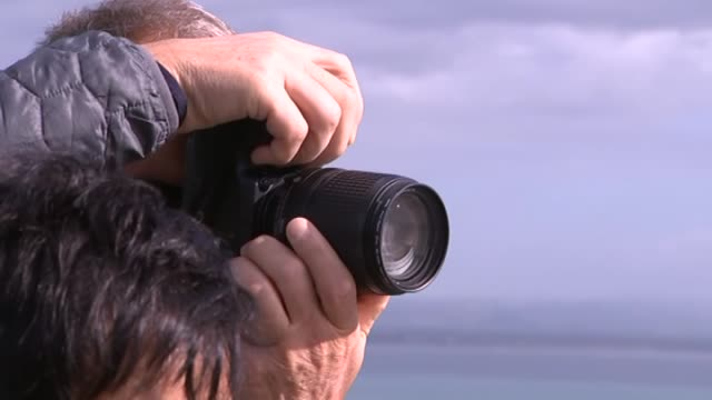 vídeos de stock e filmes b-roll de tourists standing on platforms looking out at coastline and taking photographs in the catlins in southland new zealand - vista geral