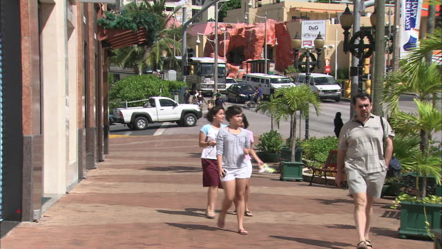 tourists stroll along a sidewalk in guam. - guam stock videos and b-roll footage