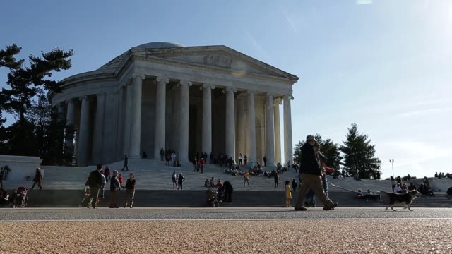 Tourists stroll by the Thomas Jefferson Memorial dedicated to Thomas Jefferson an American Founding Father and the third President of the United...