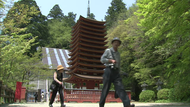 tourists stroll past the 13-tier pagoda at tanzan shrine in japan. - pagoda点の映像素材/bロール