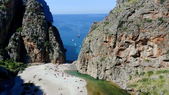 tourists sunbathing on beach at torrent de pareis, mallorca, spain - マヨルカ点の映像素材/bロール