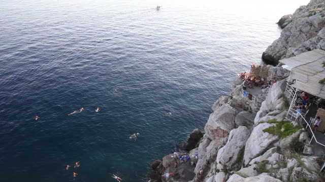 Tourists swimming in the sea, outside the city  walls of Dubrovnik