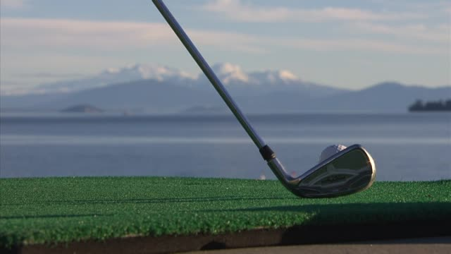 tourists swinging golf clubs and hitting balls across water at lake taupo hole in one challenge - holing stock videos & royalty-free footage