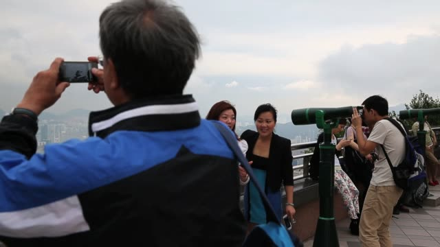 tourists take in the view from the observation deck at the peak over-looking hong kong island and kowloon peninsula in hong kong on march 20, 2013 in... - hong kong island stock videos & royalty-free footage