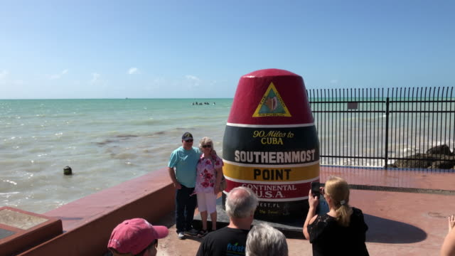 tourists take photo at the key west southernmost point - 南点の映像素材/bロール