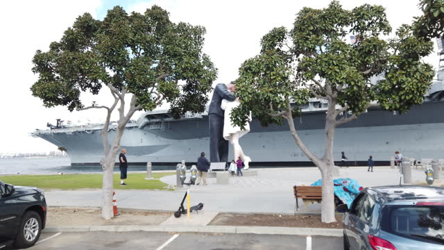 tourists take photo with the sailor kissing nurse statue in front of the uss midway museum in san diego in march 2021 amid the covid-19 pandemic - san diego stock videos & royalty-free footage